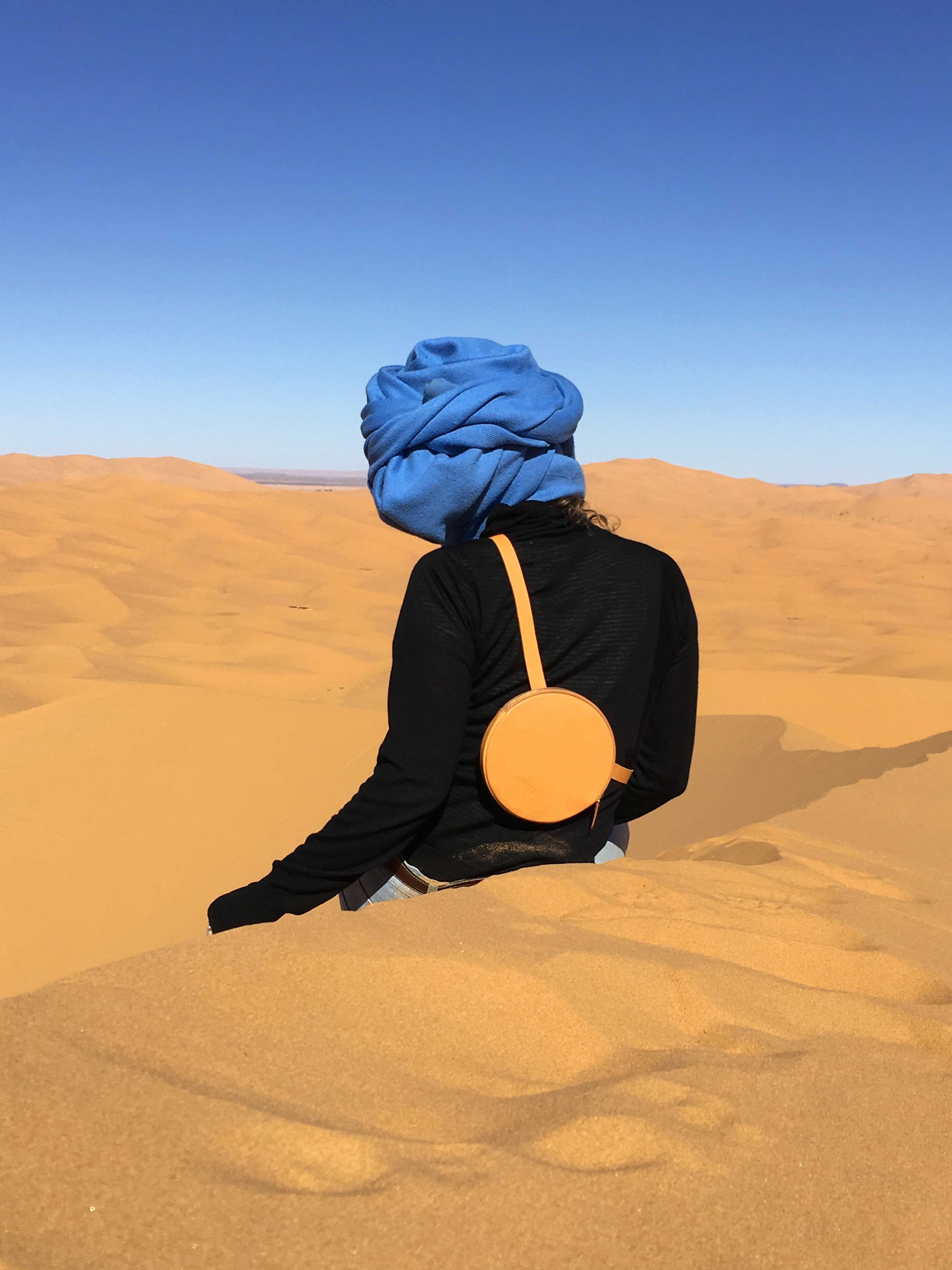 Woman in desert wearing a blue turban, a black turtleneck, a circle bag in sand color, with her back to the camera.