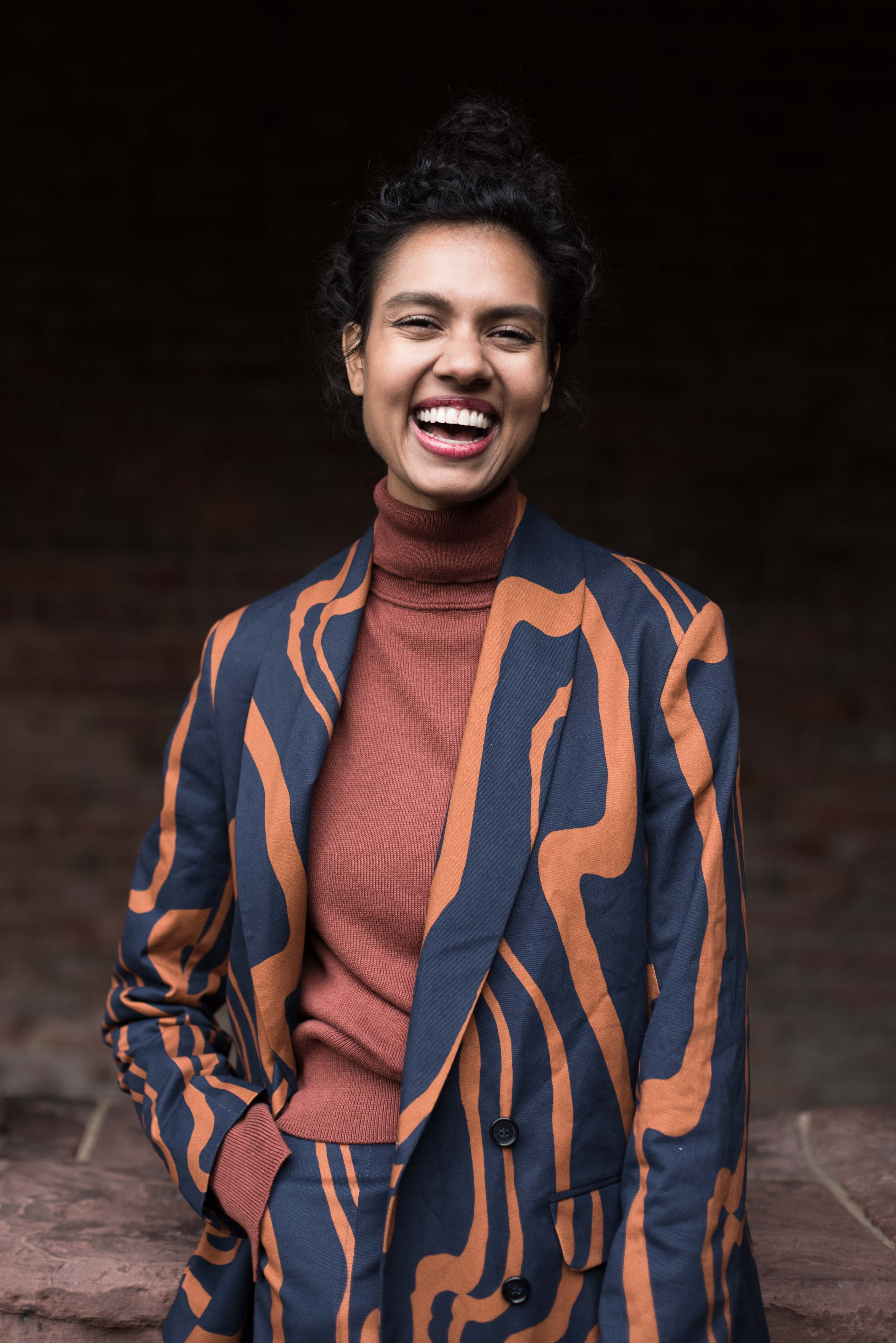 woman with hair pulled back, laughing. She is wearing a terracotta turtlneck and a navy and orange swirl print suit.