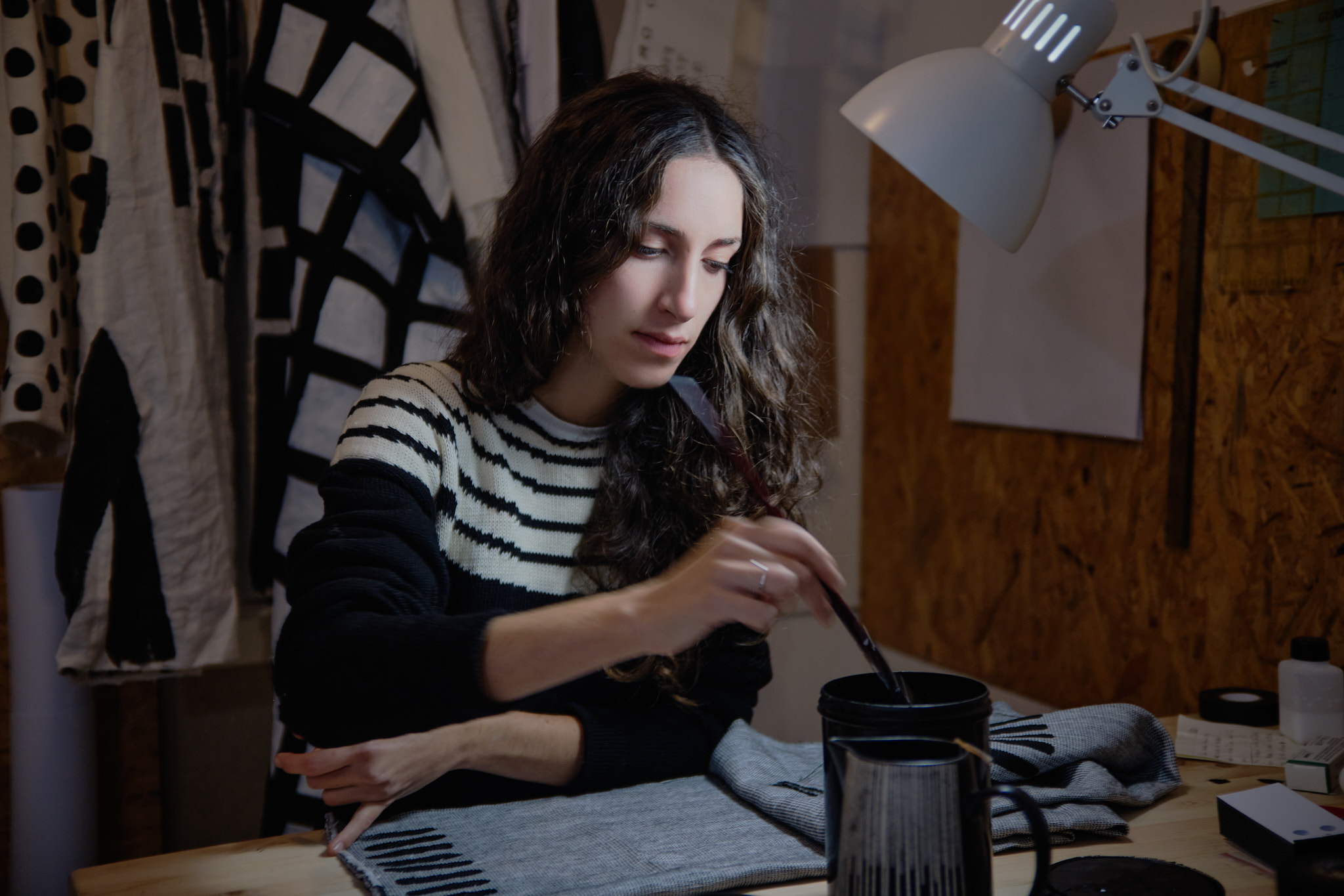 A woman (Alessandra) with long brown hair and wearing a white and black striped sweater is painting fabric at a desk