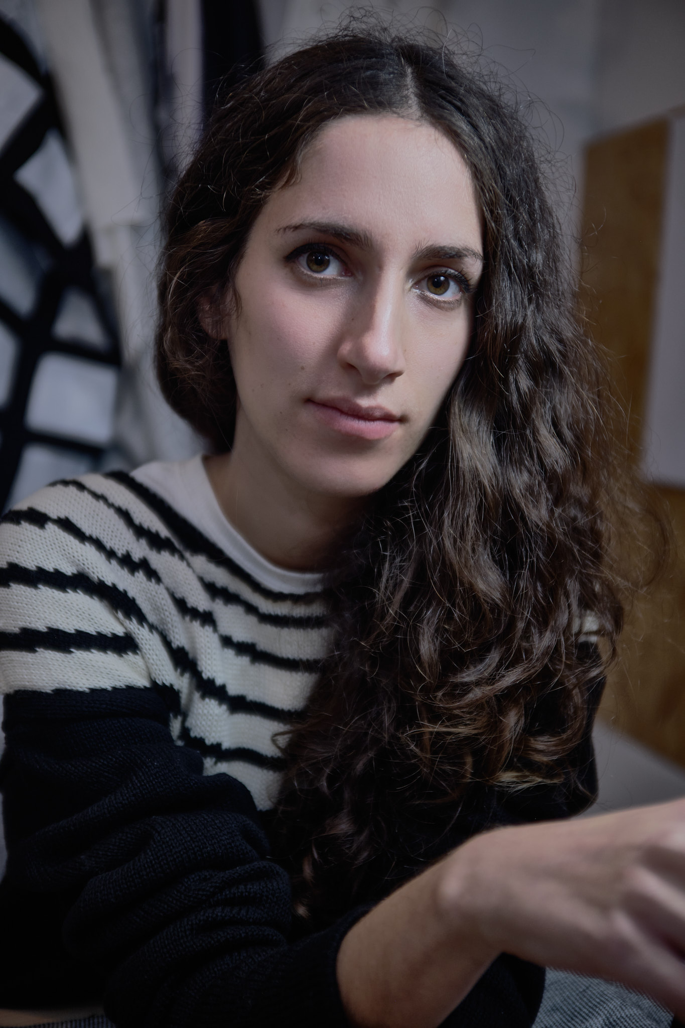 A woman with long brown hair wearing a white and black striped sweater