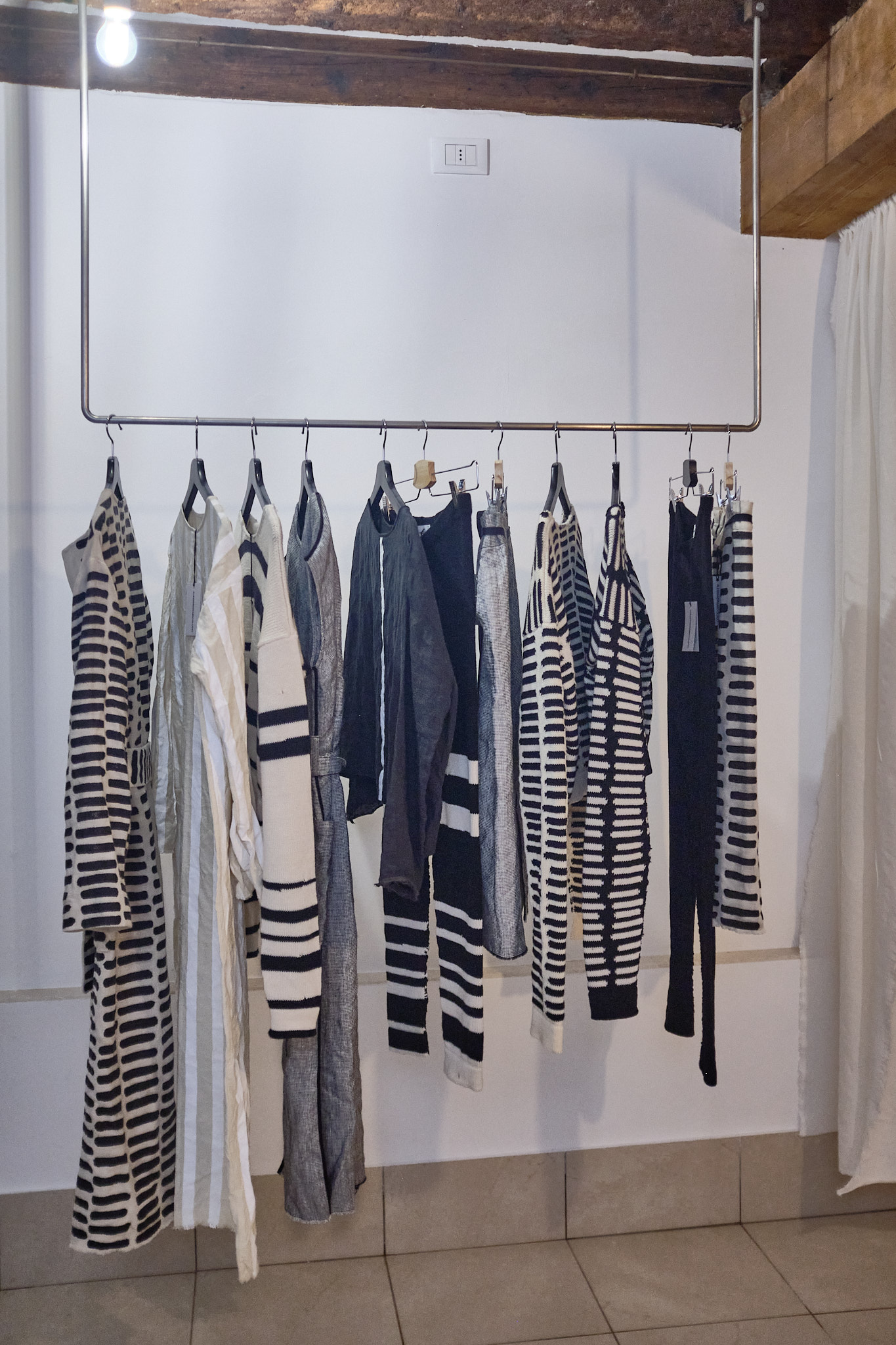 Inside of shop with black and white clothing hanging on a rail